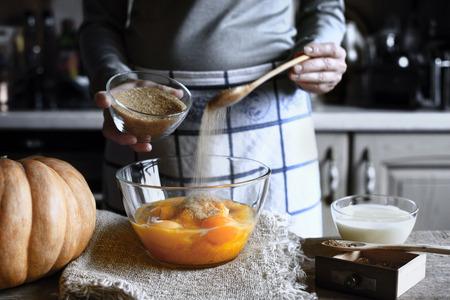 adding: Woman Adding brown sugar in the dough for pumpkin dump cake