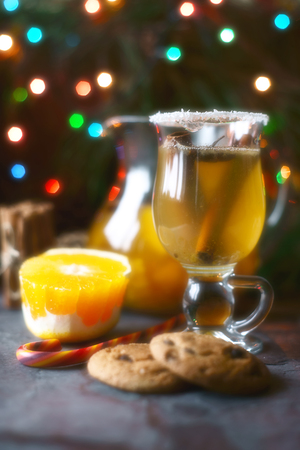 Citrus punch in the glass on the dark table with Christmas decorations Stock Photo
