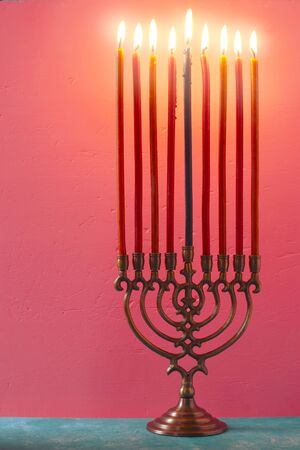 Hanukkah menorah with burning candles on the pink background vertical