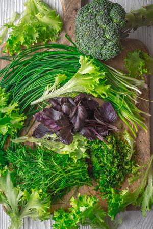 Broccoli, lettuce, basil, onion, dill on cutting board vertical Stock Photo