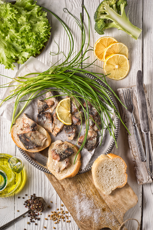 Fresh greens, sardines, bread on a wooden table vertical