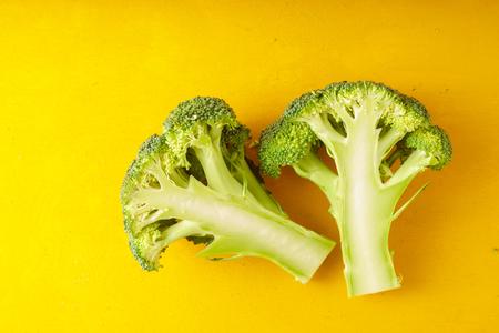 Fresh broccoli on a yellow table horizontal Stock Photo