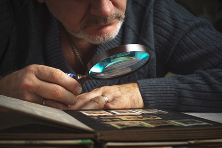 considers: Man considers album of postage stamps trough the magnifying glass horizontal Stock Photo