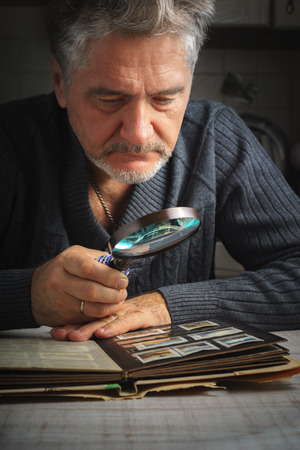 considers: Man considers album of stamps trough the magnifying glass Stock Photo