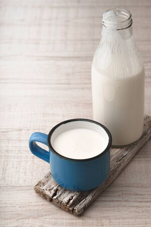 kefir: Blue cup with kefir and a bottle on a wooden stand vertical Stock Photo