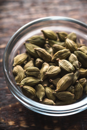 cardamum: Cardamom seeds in a bowl on a brown board vertical
