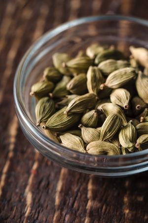 cardamum: Cordamom seeds in a bowl on a table vertical