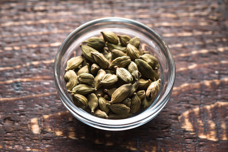 cardamum: Cordamom seeds in a bowl in the center of the table horizontal Stock Photo