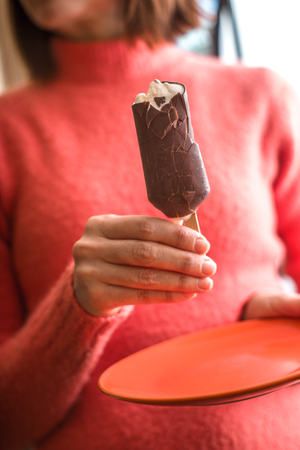 eskimo woman: Woman eating chocolate covered popsicle Stock Photo