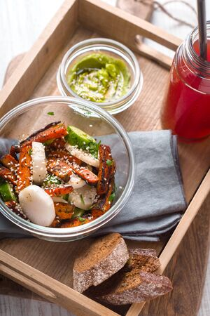 Salad, sauce, avocado, cranberry drink in a wooden box vertical Stock Photo