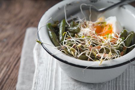 snap bean: Salad with sprouted flax and quail eggs side view Stock Photo