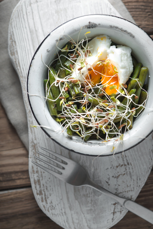snap bean: Salad with beans, sprouted flax and quail eggs in a metal bowl and fork Stock Photo