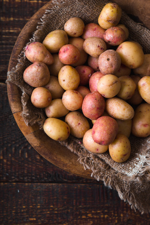 Raw potatoes red and white in a wooden bowl Stock Photo