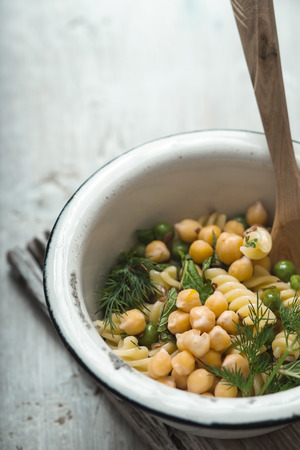 garbanzos: Salad with fusilli, chickpeas and peas in bowl on a white table