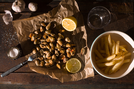brasserie: Mussels with lemons and French fries on the metal background top view horizontal