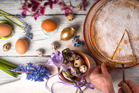 German Easter cake, a piece of cake, eggs, flowers, ribbons on a table horizontal