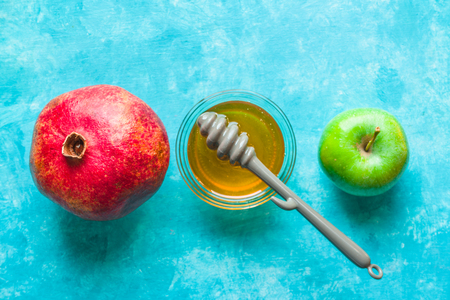 Apples, pomegranate and honey on a turquoise table line