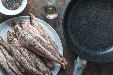 Smelt on a plate, frying pan, salt and spices close-up Stock Photo
