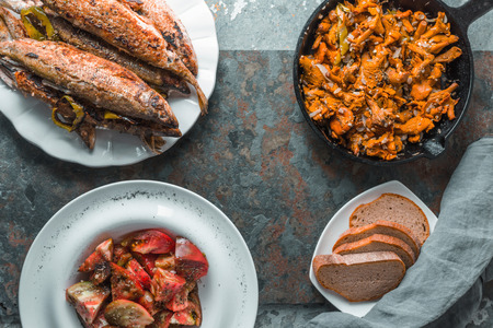 Fried chanterelles, fish on a plate, tomatoes and bread free space Stock Photo