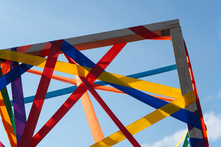 Frame of multi-colored ribbons against the blue sky