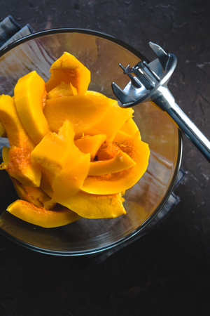 Large pieces of pumpkin in a glass bowl and blender close-up