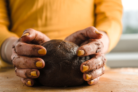 Ball of dough and cocoa in hands on a wooden board Stock Photo