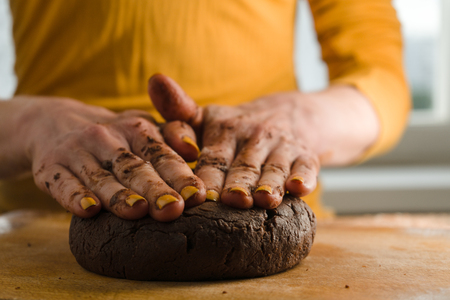light slate gray: Ball of dough and cocoa pressed to a wooden board with hands Stock Photo