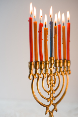 Brass hanukiya with lighted candles side view Stock Photo