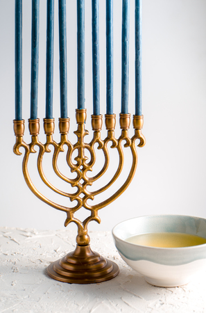 Menorah brass Hanukkah with blue candles and butter in a bowl