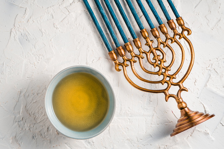 Fragment of Hanukkah with blue candles and butter in a bowl top view