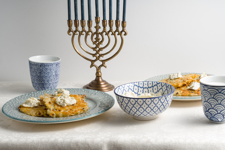 Latkes on a plate, Hanukkah, cups with milk on a white tablecloth Stock Photo