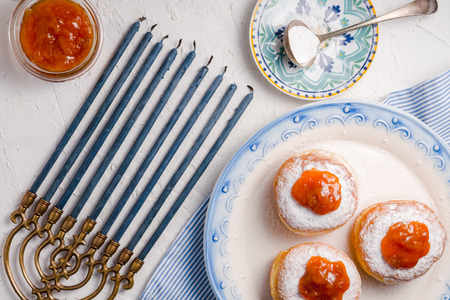 Donuts with apricot jam on a ceramic plate and Hanukkah top view Stock Photo