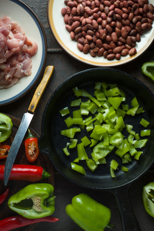 Ingredients for fajita and a knife on a cutting board.