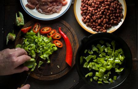 Man cuts green pepper for fajita top view Stock Photo