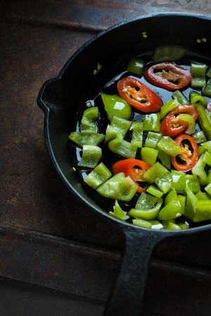 Green pepper and chili on a cast-iron frying pan closeup