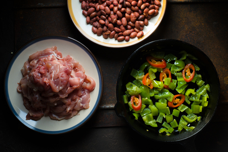 Pieces of chicken, beans. Pepper and chili in a frying pan top view