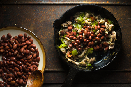 Beans are spread in a frying pan with pepper and chicken. Stock Photo