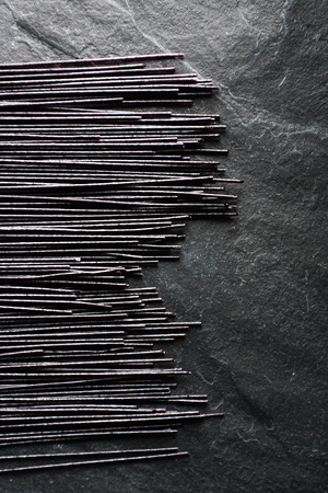 Black dry rice noodles on a black stone on the left Stock Photo