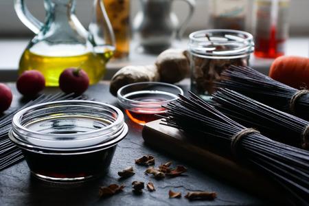 Black rice vermicelli, vinegar, olive oil and vegetables. Asian cuisine Stock Photo