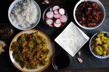 Pieces of teriyaki chicken, rice noodles and tempura broccoli. Asian cuisine