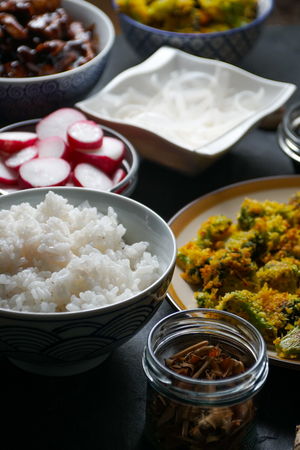 Pieces of teriyaki chicken, rice vermicelli and tempura broccoli on the table side view. Asian cuisine Stock Photo