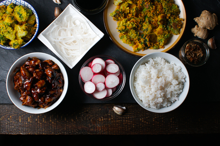 Pieces of teriyaki chicken, rice vermicelli and tempura broccoli on the table top view. Asian cuisine Stock Photo