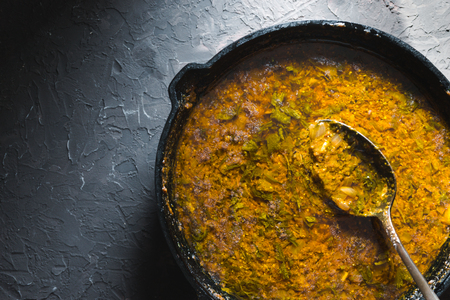Preparation of curry paste in a cast-iron frying pan. Indian food