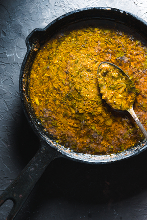 Preparation of curry paste in a cast-iron frying pan closeup. Indian food