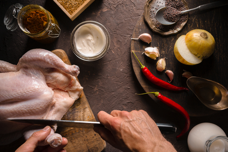 Preparation of chicken curry, chili and sour cream on the table. Indian food Stock Photo