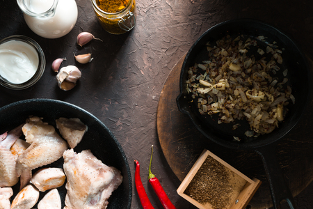 Fried chicken pieces in a frying pan, onions and chili. Indian food Stock Photo