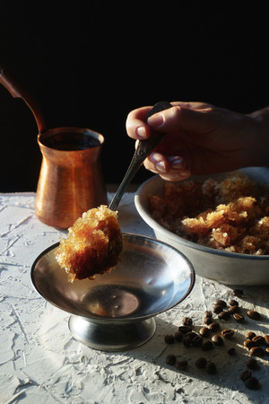 Bowl with a cold coffee dessert, a dish for dessert and grains on the table. Sicilian granite