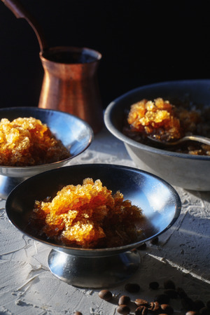 Dish for dessert with coffee ice, a bowl and grains on the table side view. Sicilian granite