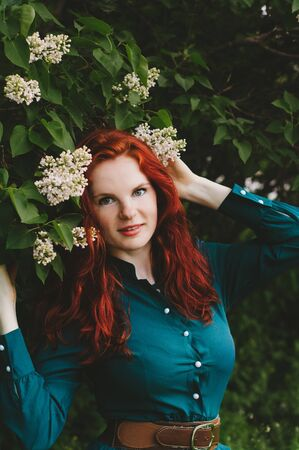Red-haired girl with freckles standing near a lilac bush