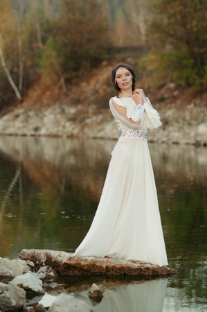 Girl in a white dress on the shore of a pond at sunset of the day Stock Photo